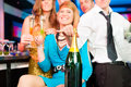 People in club or bar drinking champagne young and having fun all are looking into the camera Stock Photo