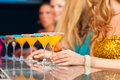 People in club or bar drinking cocktails Royalty Free Stock Photos