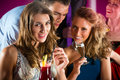 People in club or bar drinking cocktails young and having fun Royalty Free Stock Photos