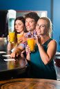 People in club or bar drinking young cocktails and having fun Stock Images