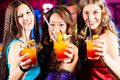 People with cocktails in bar or club group of party three female girl friends a having fun Royalty Free Stock Photo