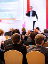 People at the conference speaker on podium hall rear view Royalty Free Stock Photo