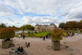 People enjoy autumn sunny day in the luxembourg garden on october paris palace is official residence of Royalty Free Stock Photo