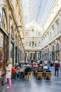 People enjoying the shops and sidewalk cafes in the Saint-Hubert Royal Galleries in Brussels, Belgium Royalty Free Stock Photo