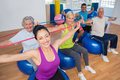 People exercising with resistance bands in gym portrait of fit on fitness balls Royalty Free Stock Images