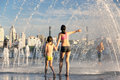 People fleeing from the heat in a city fountain in the centre of a European city