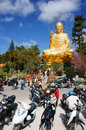 People go to pagoda da lat vietnam jan pray lucky yellow statue of buddha in blue sky crowd of buddhist visit with belief faith Stock Photo