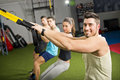 People at gym doing trx exercises elastic rope crossfit room Stock Photos