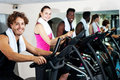 People at gym working out happily smiling young cycling the fitness centre Royalty Free Stock Photos