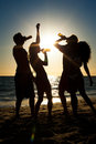 People having party at beach with drinks two couples on the a drinking and a lot of fun in the sunset only silhouette of to be Stock Photo