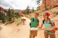 People hiking looking at hike map in bryce canyon young multiracial couple of hikers navigating and smiling happy during Stock Photo
