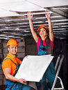 People installing suspended ceiling in builder uniform Royalty Free Stock Photo