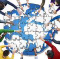 People with Jigsaw Puzzle Forming Globe Royalty Free Stock Photo