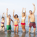 People jumping in the sea group of friends Stock Image
