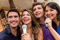 People karaoke singing group of at the bar having fun Royalty Free Stock Image