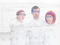People lab analysis close up seen through a transparent board ot three scientists in a chemistry pointing and analyzing formulas Royalty Free Stock Photos