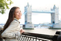 People in london woman happy by tower bridge multicultural young professional smiling and laughing enjoying view of river thames Stock Image