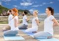 People making yoga in hero pose outdoors