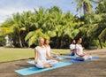 People meditating in yoga lotus pose outdoors