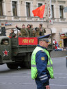 People in military iniform carrying a red flag driving the car policeman is watching the order victory day celebration on the Stock Image