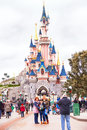People near castle in the Disneyland Paris are taking photo.