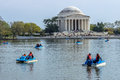 People in paddle boats in the lake in front of the millions tourists each year flock to washington dc to see famous cherry blossom Royalty Free Stock Photo