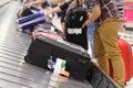 People picking up suitcase on luggage conveyor belt