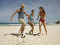 People playing football on the beach young Royalty Free Stock Photo