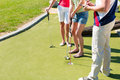 People playing miniature golf outdoors man and women on a beautiful summer day Royalty Free Stock Photos