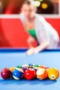 People playing pool billiard game couple or friends with queue and balls on table Stock Image
