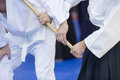 People practice Aikido with wooden jo