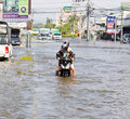 People push motorcycle on water flood road Stock Photo
