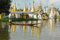 People rowing boat on Inle lake with pagoda background in Shan, Myanmar Royalty Free Stock Photo