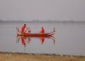 People rowing boat on lake at sunrise in Mandalay, Myanmar