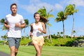 People running in city park active lifestyle happy young couple living an healthy jogging training their cardio during summer on Royalty Free Stock Images