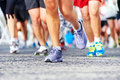 People running marathon race competing in fitness and healthy active lifestyle feet on road Royalty Free Stock Images