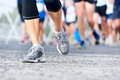 People running marathon race competing in fitness and healthy active lifestyle feet on road Stock Photo