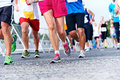 People running marathon race competing in fitness and healthy active lifestyle feet on road Stock Photos