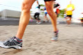 People running marathon race competing in fitness and healthy active lifestyle feet on road Stock Images