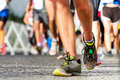 People running marathon race competing in fitness and healthy active lifestyle feet on road Royalty Free Stock Photo