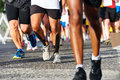 People running marathon race competing in fitness and healthy active lifestyle feet on road Stock Photography