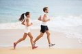 People running runner couple on beach run jogging outdoors fit men athlete and women fitness runners working out together Stock Photo