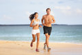 People running young couple jogging on beach attractive fit sporty runners side by side the in the summer Stock Photography