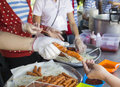 People's hand is taking fried sausage stick Royalty Free Stock Photo