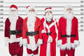 People in Santa costume standing side by side against police lineup Royalty Free Stock Photo