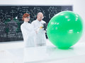 People scanning objects general view of teacher and student in a chemistry lab a green balloon and a blackboard on the background Stock Image