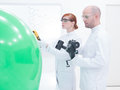 People scanning objects in lab close up of teacher and student a chemistry a green balloon and a white board on the background Stock Image
