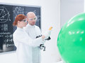 People scanning objects in laboratory side view of teacher and student a chemistry lab a green balloon and a blackboard on the Royalty Free Stock Images