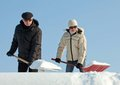 People shovelling snow on a roof Royalty Free Stock Photography