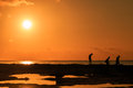 People silhouetted against a tropical sunset Royalty Free Stock Photo